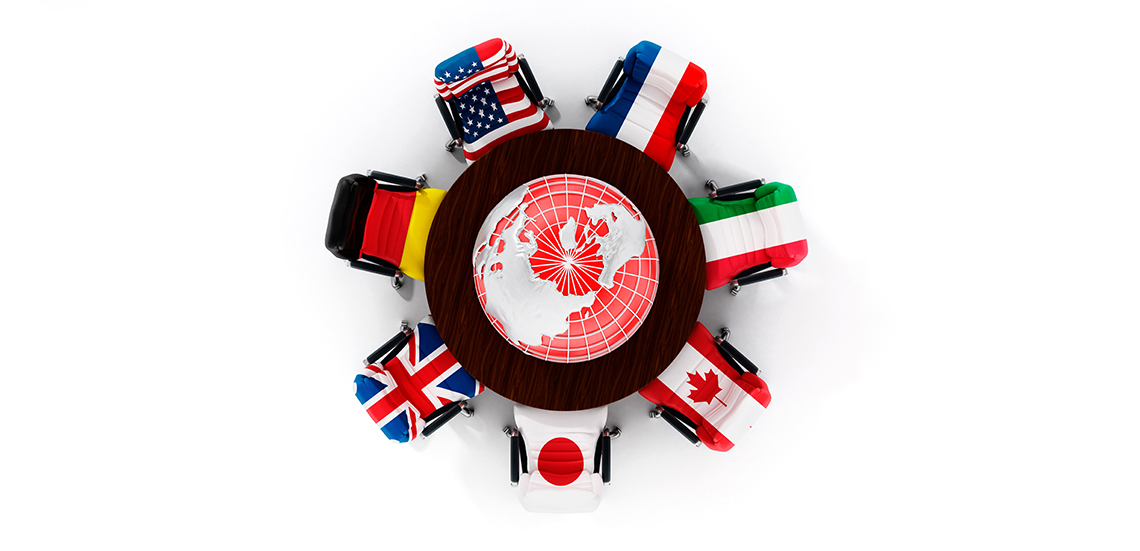 G7 country flags around table with globe