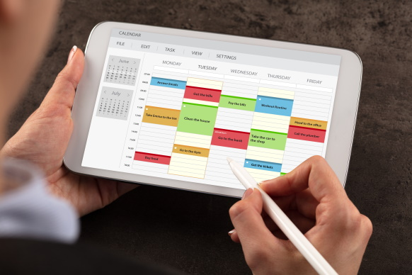 Hand with stylus updating digital calendar